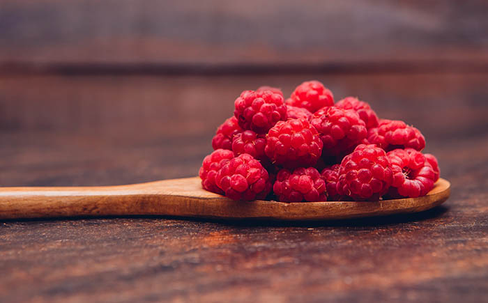 Red raspberries in a wooden spoon side view on a wooden background
